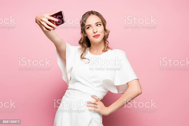 Portrait of a young attractive woman making selfie photo with on a picture id856158972?b=1&k=6&m=856158972&s=612x612&h=egxncjxnhwu4qutef3psbkndxdemw5pxmihuhmuxna0=