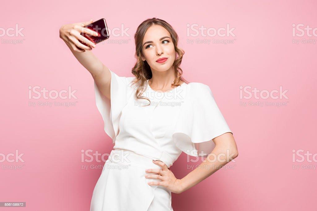 Retrato de una joven atractivo que selfie foto con el smartphone en un fondo rosa - foto de stock