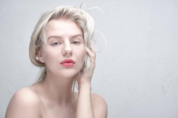 Porträt einer jungen, schönen blonden Frau mit plumpen roten Lippen und nackten Schultern, die ihr Haar auf weißem Hintergrund berühren. Modische, ausgefallene Frisur – Foto