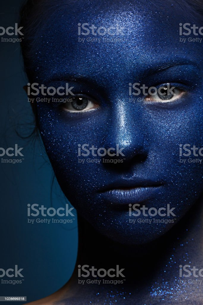Portrait of a young beautiful girl. The face is painted with blue...