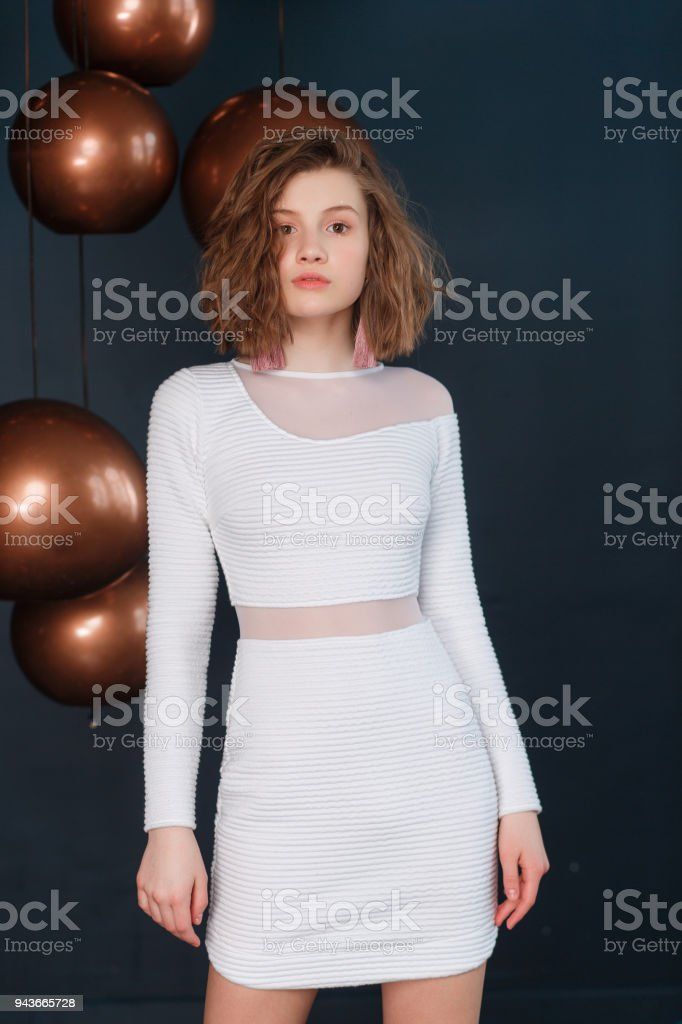 132f8dd8d9 Portrait of a young beautiful girl wearing white skirt and blouse on black  background with copper