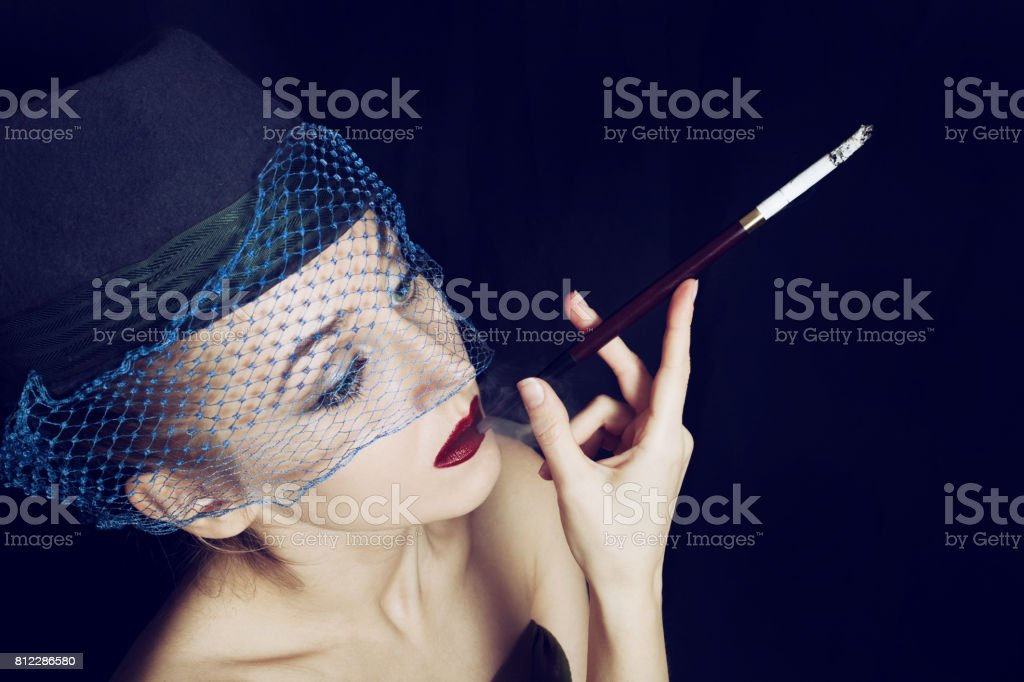 Portrait of a young beautiful woman dressed in a hat with a veil stock photo