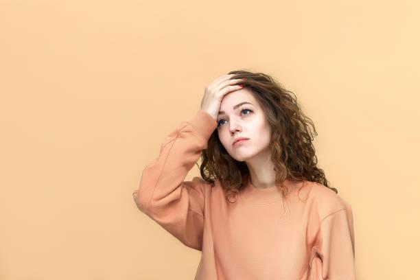 ritratto di una giovane bella donna che indossa una felpa in posa isolata su sfondo giallo - tenersi la testa tra le mani foto e immagini stock