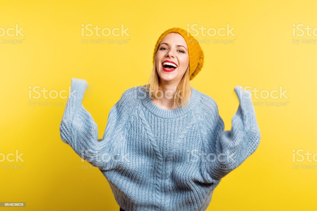 Portrait of a young beautiful woman with a woolen hat in studio on a yellow background. royalty-free stock photo