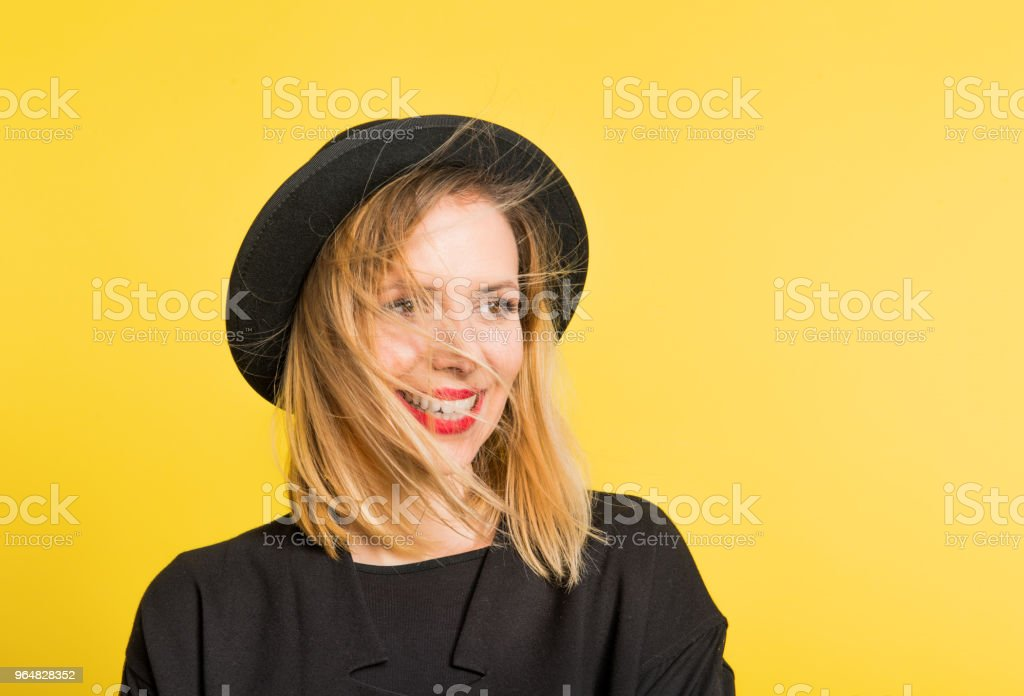 Portrait of a young beautiful woman with black hat in studio on a yellow background. royalty-free stock photo