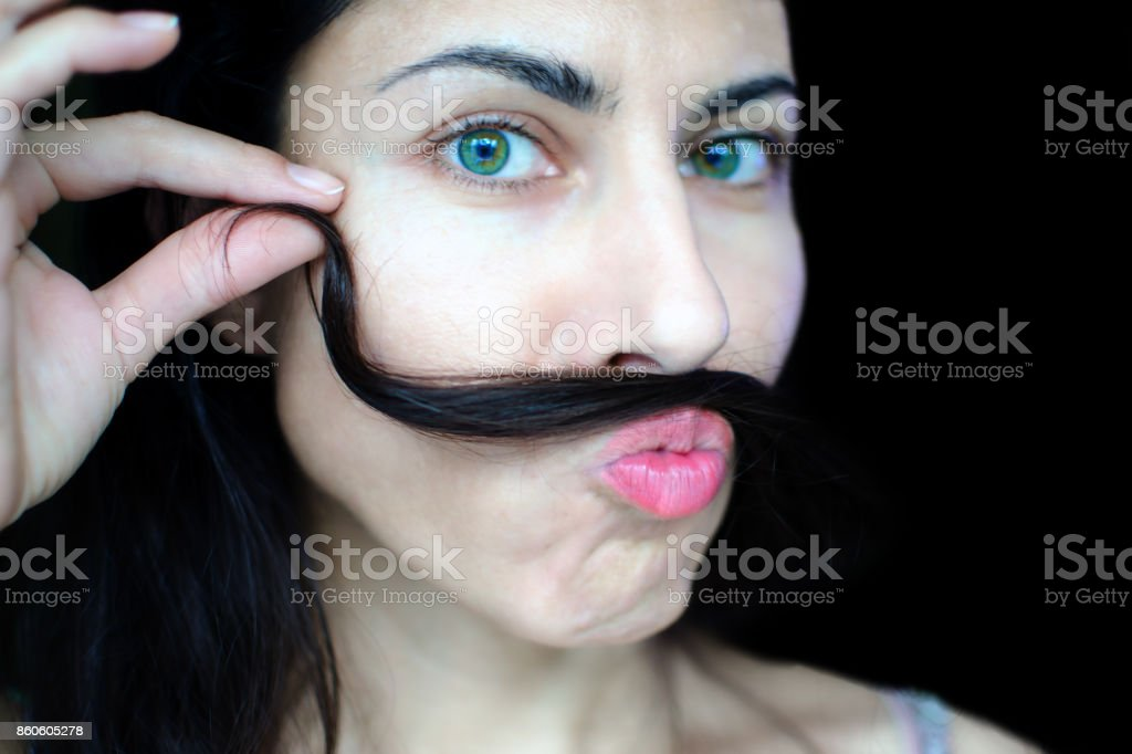 Portrait of a young beautiful woman with dark hair holding a strand of her hair over her upper lip. The concept of the problem of removing excess hair on the face of women. stock photo
