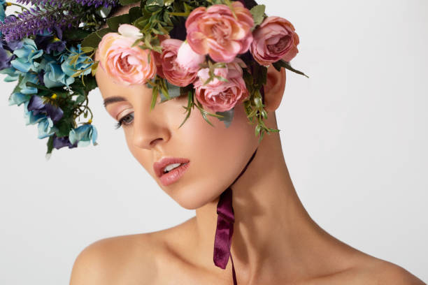 Portrait of a young beautiful woman with different flowers on her head. Spring fashion photo. Skin care concept, beauty spa, bio product. stock photo