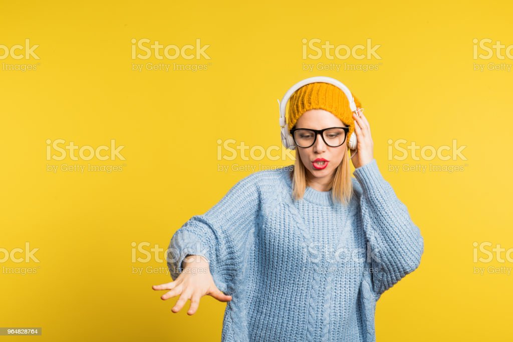Portrait of a young beautiful woman with headphones in studio on a yellow background. royalty-free stock photo