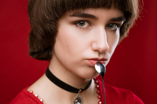 Portrait of a young beautiful woman with short hair and a thoughtful look holding a spoon in her hand near her face. Close-up on a red background. stock photo