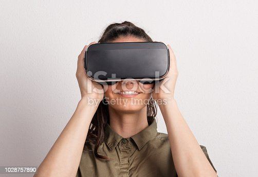 istock Portrait of a young beautiful woman with VR goggles in studio. 1028757890