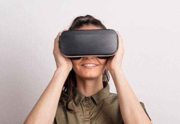 Portrait of a young beautiful woman with VR goggles in studio. stock photo