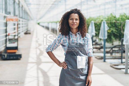Smiling female farmer in a greenhouse