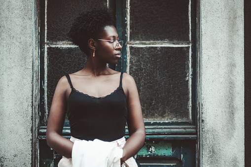 Portrait of the young black female in a tank topand spectacles looking aside while standing in front of an old antique wooden door with glass inserts and holding a white trench in her hands