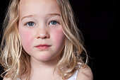 Close up portrait of a young girl on black background.