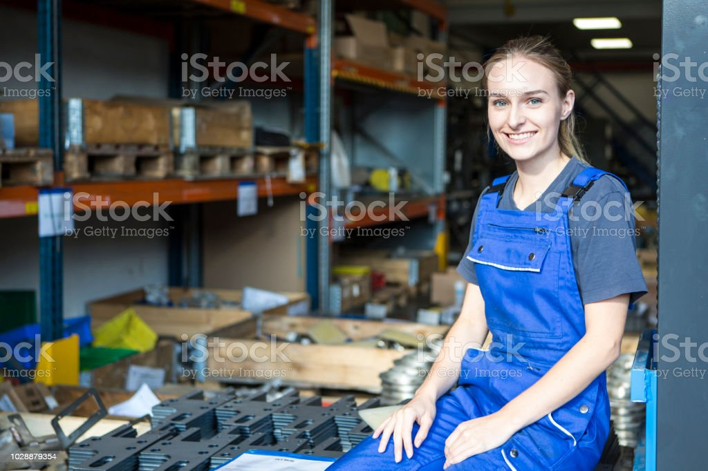 Portrait of a young laughing female trainee in metal industry