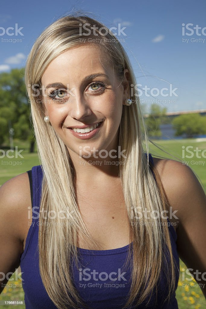 Portrait of a young blond woman smiling outside royalty-free stock photo