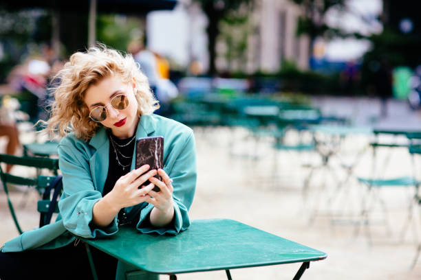 portrait of a young blonde sitting at a table outside with phone - carlos david stock pictures, royalty-free photos & images