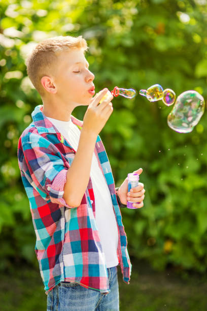 Portrait of a young boy blowing soap bubbles stock photo