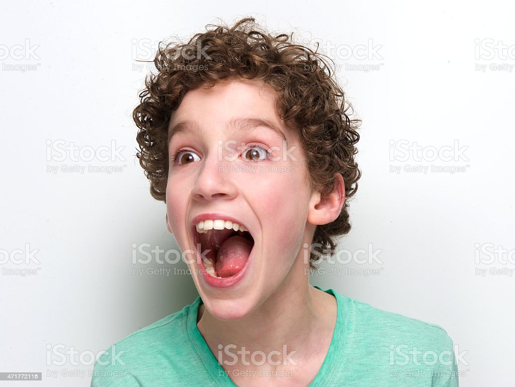 Portrait of a young boy looking happily surprised stock photo
