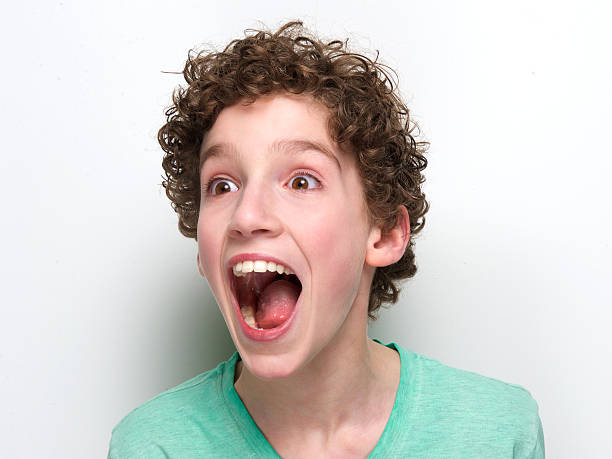 Portrait of a young boy looking happily surprised Close up portrait of a boy with mouth open having a surprised expression mouth open stock pictures, royalty-free photos & images