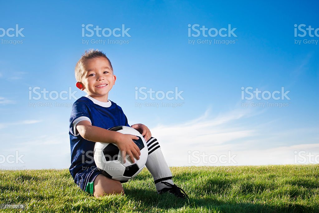 Portrait of a young boy wearing a soccer uniform in a field stock photo