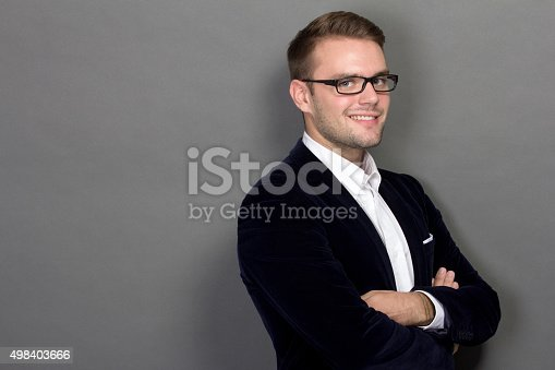 498403166 istock photo Portrait of a young businessman in suit smiling, crossed arms 498403666