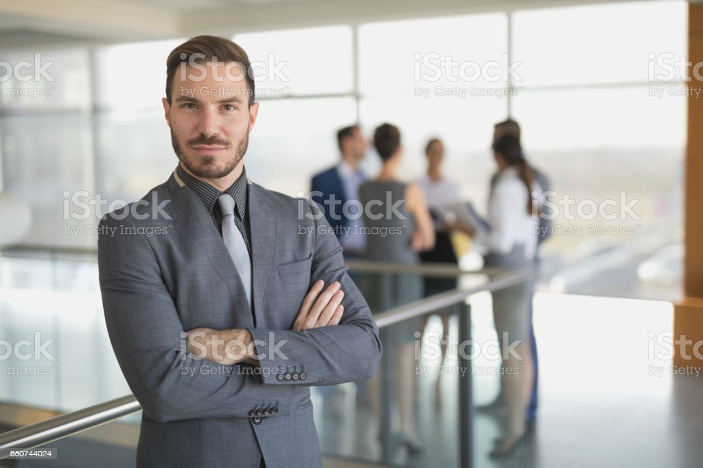 Portrait of a young businessman with arms crossed stock photo