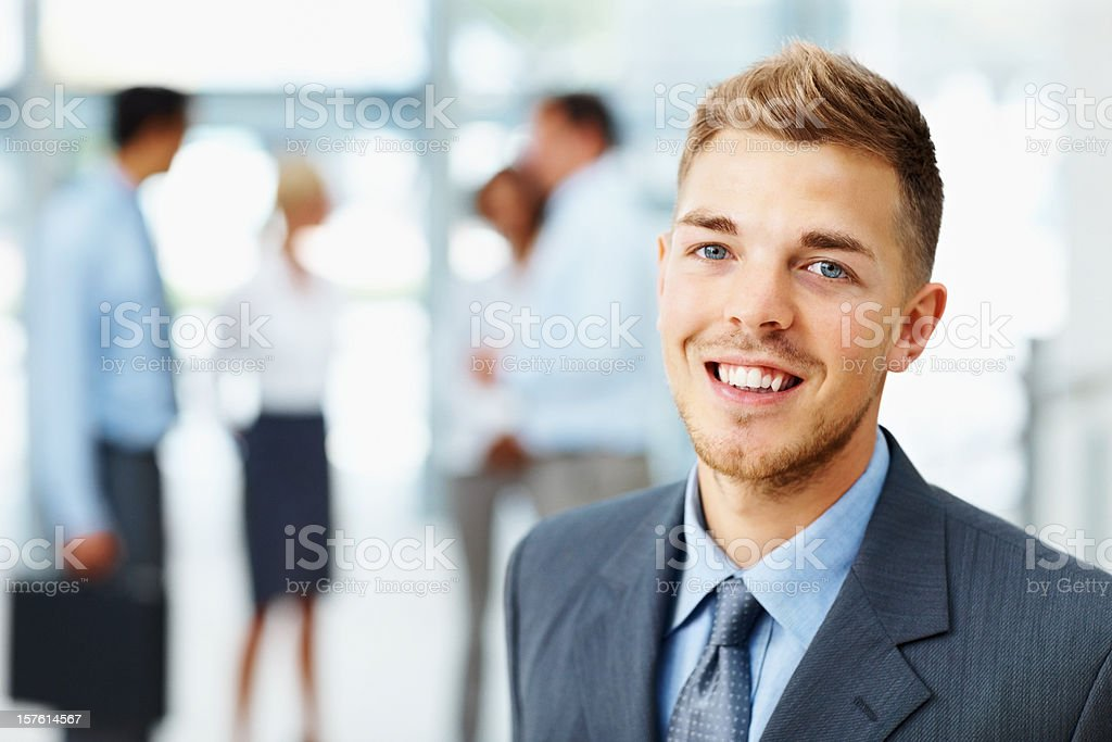Portrait of a young businessman with colleagues in the background royalty-free stock photo
