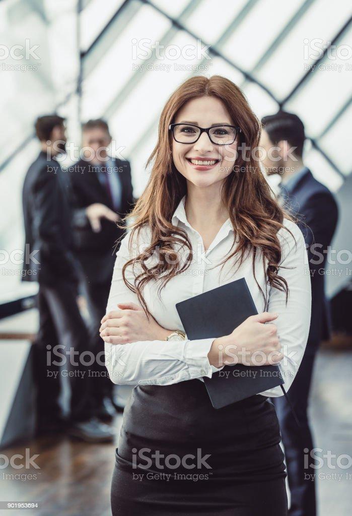 Porträt von eine junge Geschäftsfrau mit Kollegen hinter – Foto