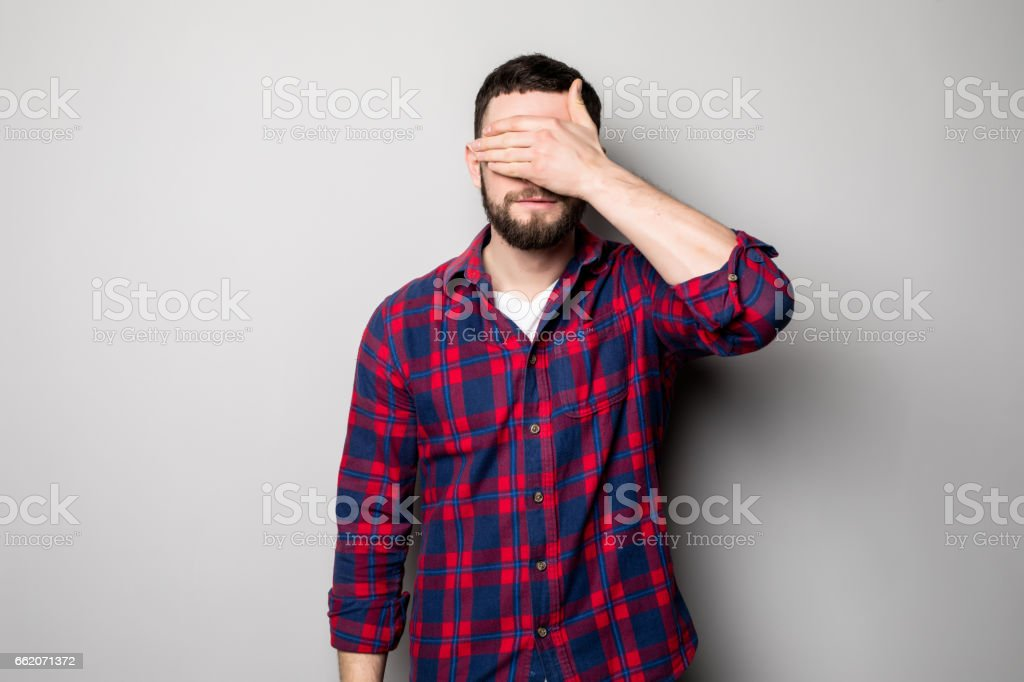 Portrait of a young casual man covering eyes with hand royalty-free stock photo