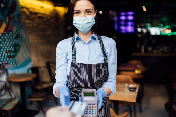 Portrait of a young Caucasian female waitress holding credit card reader stock photo