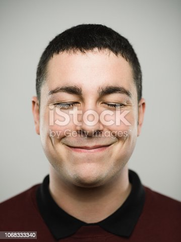 Close-up portrait of real young man with closed eyes and with a comfortable attitude. Caucasian male has brown hair. He is against gray background. Vertical studio photography from a DSLR camera. Sharp focus on eyes.