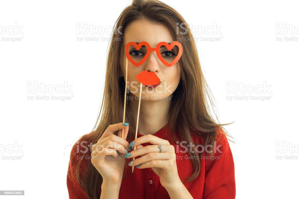 Portrait of a young charming girl who keeps near the face paper Dummies close-up stock photo