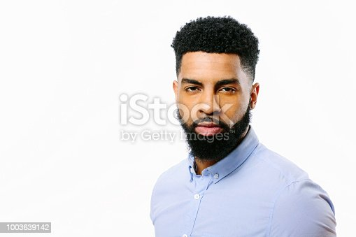Portrait of a young cool man with beard and black curly hair, isolated on white background