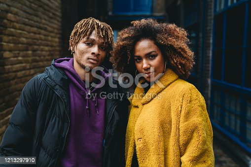 Portrait of a young couple in the street. They are wearing colorful clothes and looking at camera. Shoreditch, London.