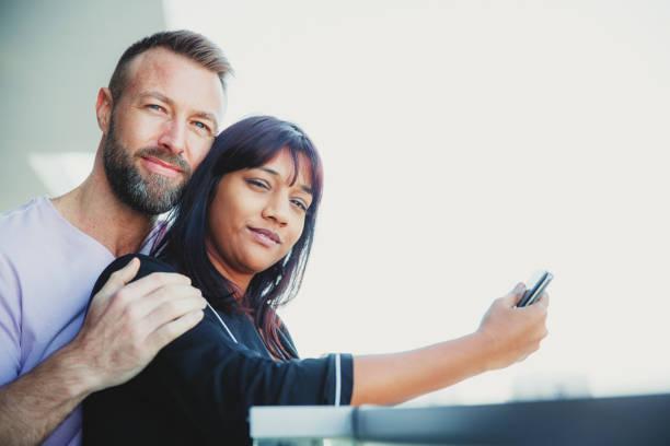porträt eines jungen paares, das auf dem balkon steht - hochzeitsreise dubai stock-fotos und bilder