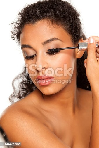 istock portrait of a young dark-skinned woman applying mascara on a white background 1144489565