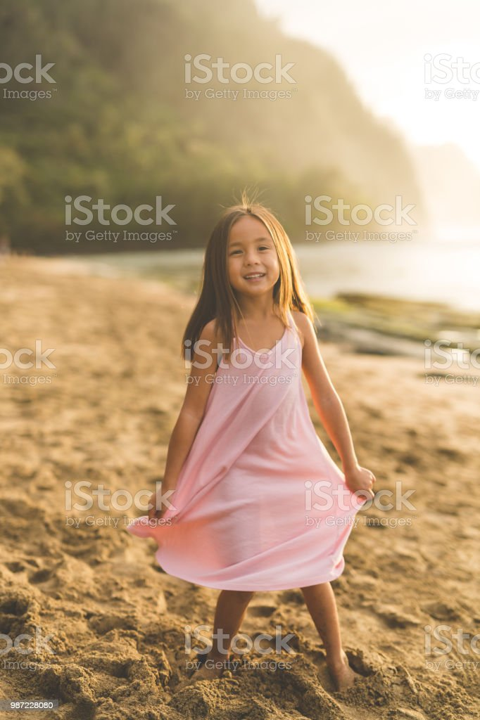 c9df472d6cc3 Portrait of a young ethnic girl twirling in sundress on the beach foto  stock royalty-