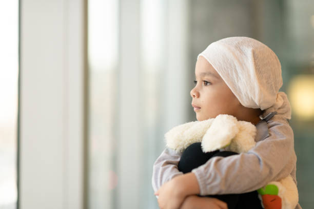 Portrait of a young ethnic girl with cancer A beautiful little girl with cancer takes a break from treatment. She is sitting near a large bay of windows in the hospital's corridor. The girl is wearing a headscarf and is hugging a stuffed rabbit toy. She is looking out the window with a peaceful expression. cancer cell stock pictures, royalty-free photos & images