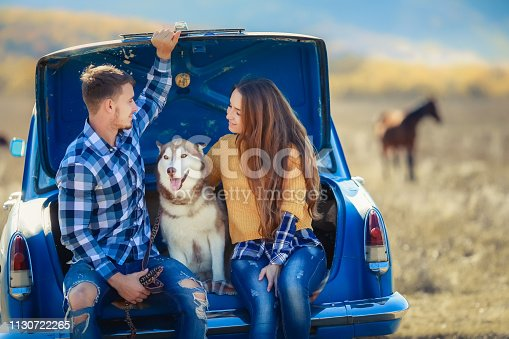 Portrait of a young family with a dog near a convertible