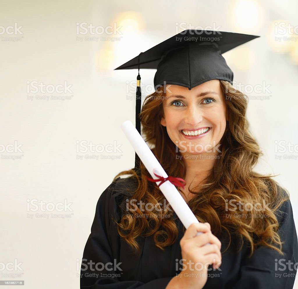 Portrait of a young female graduate holding her degree royalty-free stock photo
