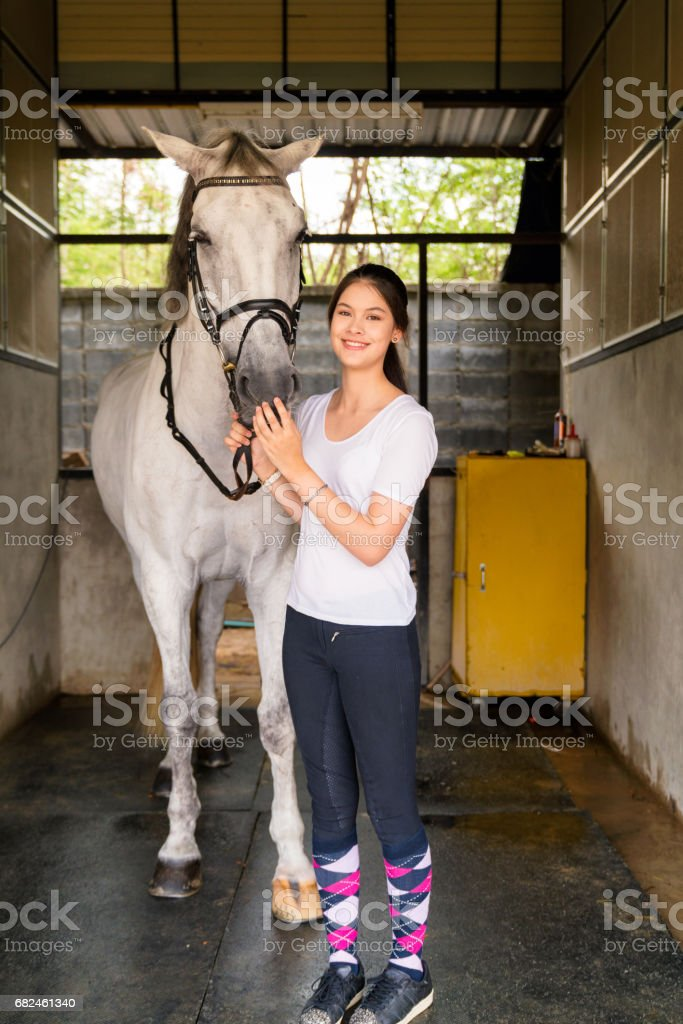 Portrait of a young female horse rider stood with her horse royalty-free stock photo