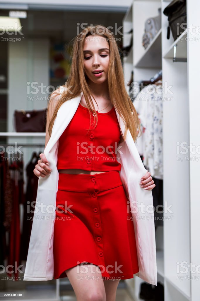 caffa016293 Portrait of a young female model looking in mirror wearing red top and  skirt co-ord set and long vest standing in a show room - Stock image .