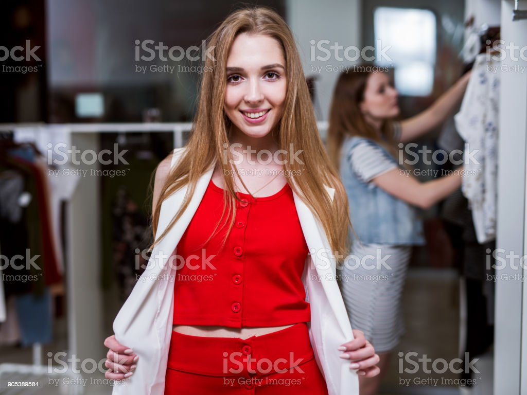 a41a7e871f Portrait of a young female model looking in mirror wearing red top and skirt  co-