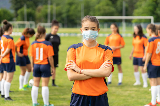 COVID-19. Portrait of a young football player wearing face mask due to coronavirus pandemic.