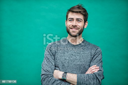 Portrait of a young french man on a green background.