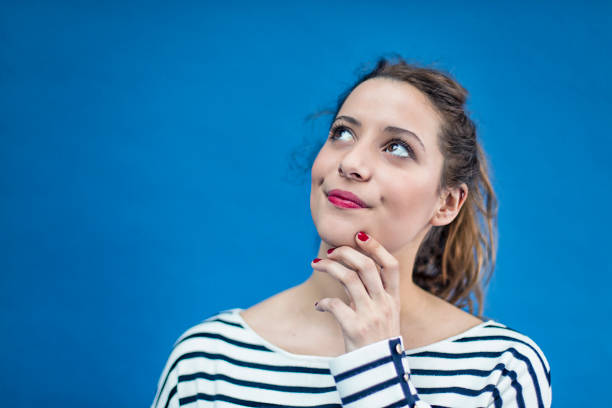 Portrait of a young french woman Portrait of a young french woman on a blue background. raised eyebrows stock pictures, royalty-free photos & images