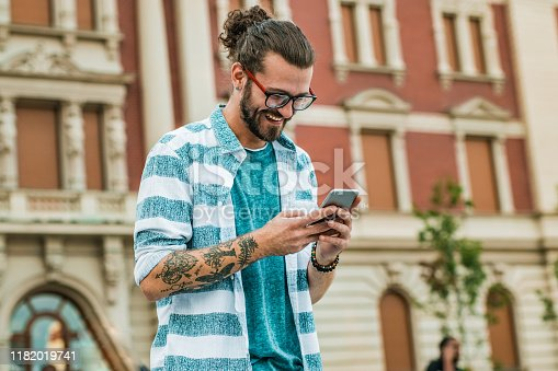 A portrait of a hipster guy holding a smartphone. He is laughing and he is waiting for a cab