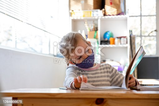 A young girl sitting in her classroom back at school wearing a protective face mask after the COVID 19 lockdown. Schoolgirl wearing a protective face mask