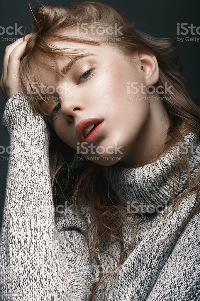 Portrait of a young girl in sweater studio stock photo